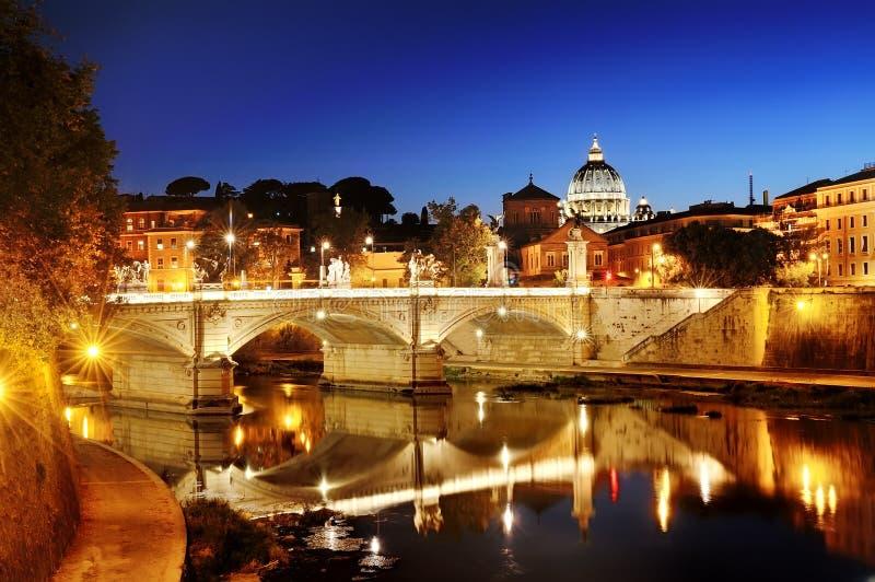 Roma, Italia - vista de un puente sobre el río de Tíber y San Pedro y x27; bóveda de la basílica de s en Vaticano en la noche imagen de archivo