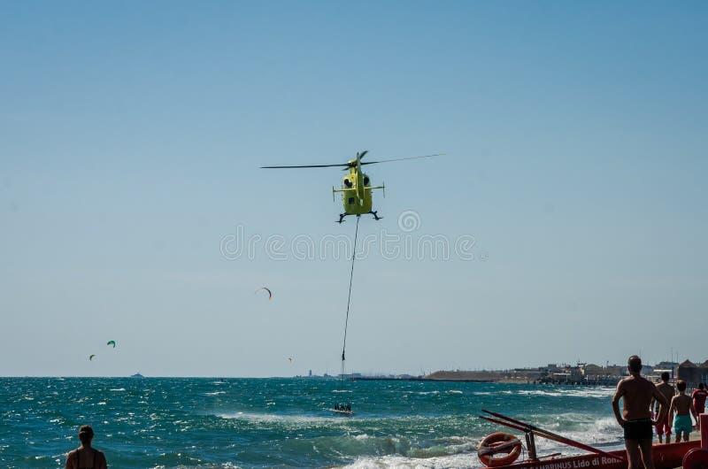 ROMA, ITALIE - JUILLET 2017 : Un hélicoptère du feu prend l'eau dans un panier pour s'éteindre un feu en mer tyrrhénienne près d' photographie stock