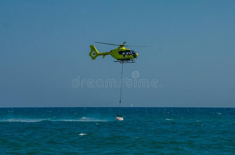 ROMA, ITALIE - JUILLET 2017 : Un hélicoptère du feu prend l'eau dans un panier pour s'éteindre un feu en mer tyrrhénienne près d' photo libre de droits