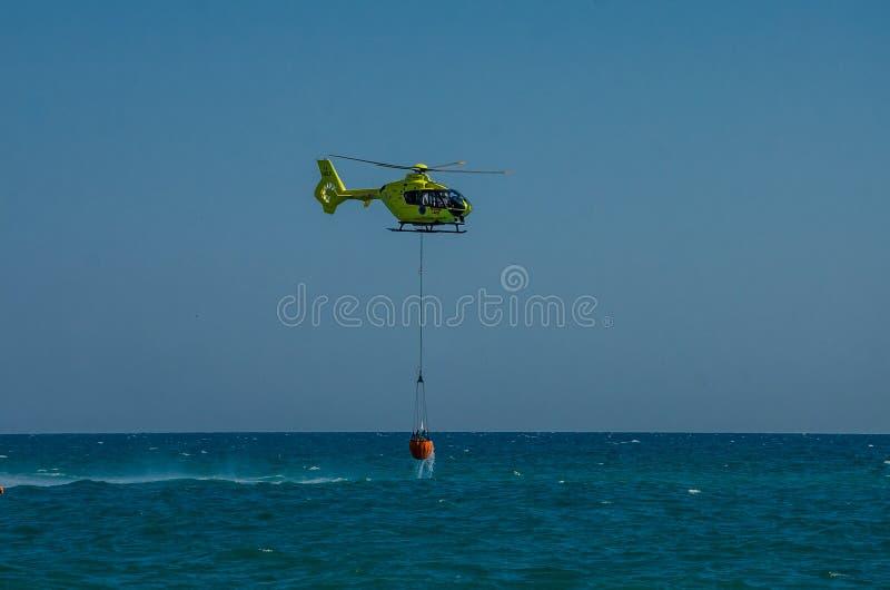 ROMA, ITALIE - JUILLET 2017 : Un hélicoptère du feu prend l'eau dans un panier pour s'éteindre un feu en mer tyrrhénienne près d' photographie stock libre de droits