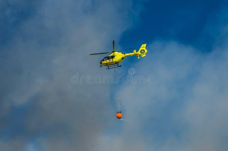 ROMA, ITALIE - JUILLET 2017 : Un hélicoptère du feu prend l'eau dans un panier pour s'éteindre un feu en mer tyrrhénienne près d' photos stock