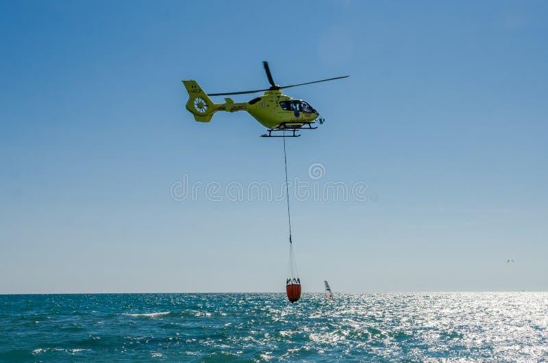 ROMA, ITALIE - JUILLET 2017 : Un hélicoptère du feu prend l'eau dans un panier pour s'éteindre un feu en mer tyrrhénienne près d' photo stock