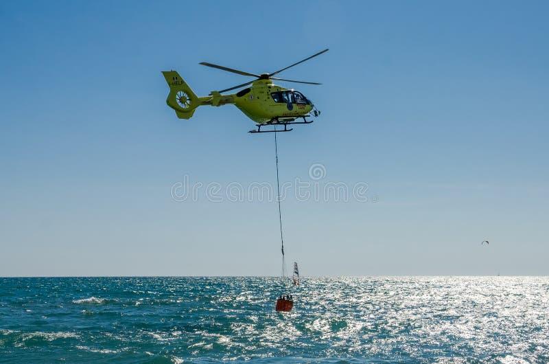 ROMA, ITALIE - JUILLET 2017 : Un hélicoptère du feu prend l'eau dans un panier pour s'éteindre un feu en mer tyrrhénienne près d' images libres de droits