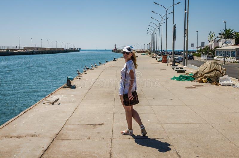 ROMA ITALIEN - JULI 2017: Ung charmig flicka i ett lock med vapenskölden av Malta och exponeringsglas, promenader längs invallnin royaltyfria bilder