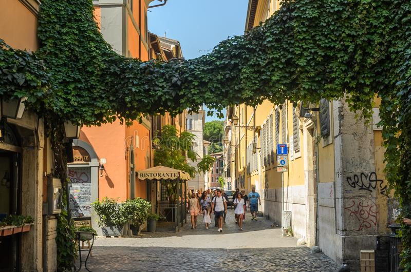 ROMA, ITALY - AUGUST 2018: Tourists walk through the narrow ancient streets of Rome royalty free stock photography