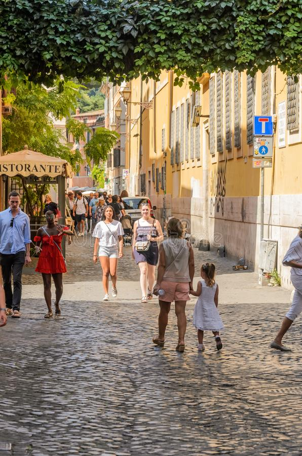 ROMA, ITALY - AUGUST 2018: Tourists walk through the narrow ancient streets of Rome stock photo
