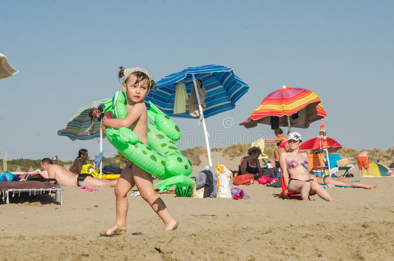 ROMA, ITALY - JULY 2017: Little charming girl playing on a sandy beach with an inflatable circle with a girlfriend and swimming in royalty free stock photo