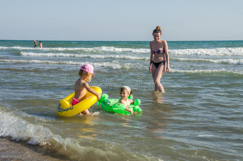 ROMA, ITALY - JULY 2017: Little charming girl playing on a sandy beach with an inflatable circle with a girlfriend and swimming in. Little charming girl playing stock photos
