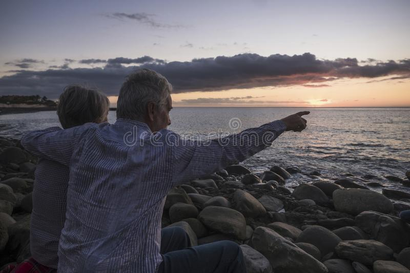Romaanse activiteit voor volwassen hogere paarzitting bij het strand die een gekleurde zonsondergang op het overzees - vakantie e stock fotografie