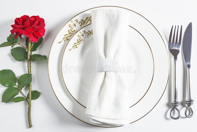 Romaanse tafel voor Valentijnsdiner Witte servet met ring op witte platen, stock afbeeldingen