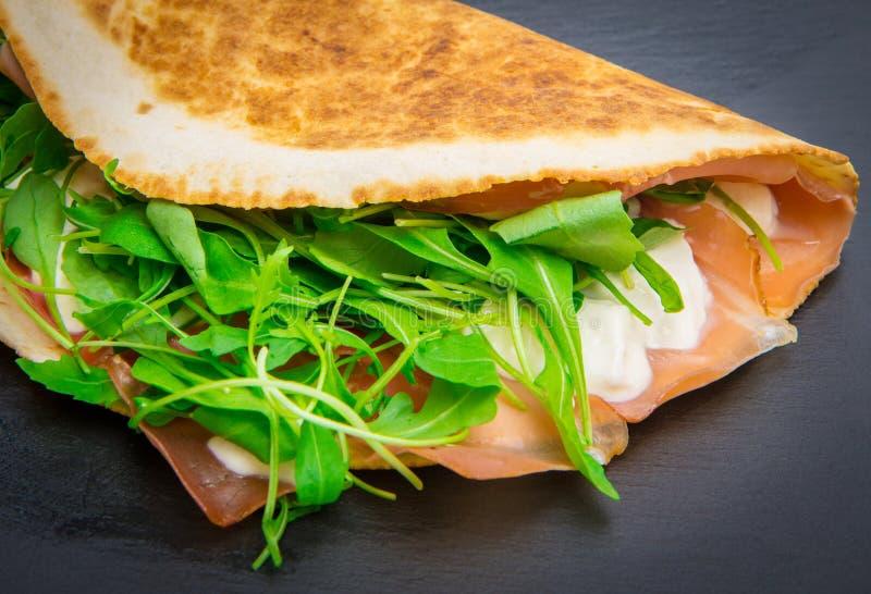 Romagnola tipico di piadina con il prosciutto, il formaggio ed il razzo fotografie stock libere da diritti