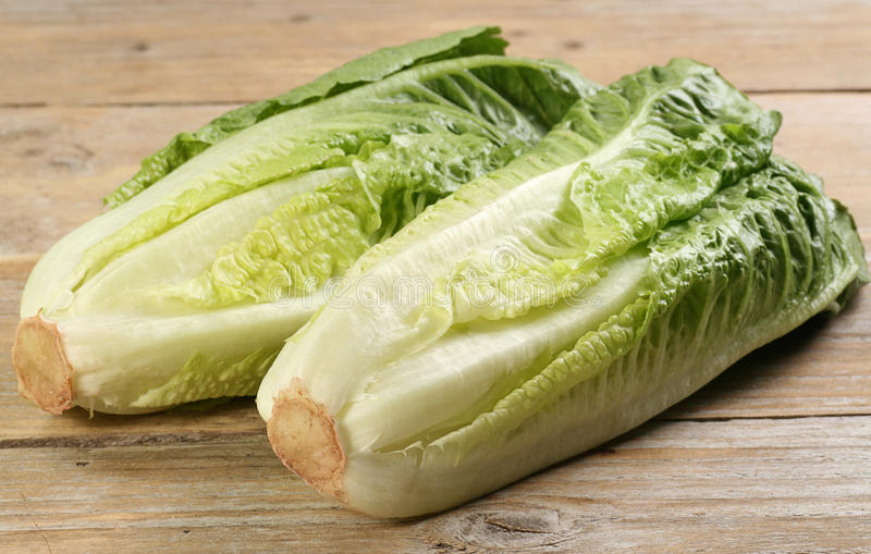 Romaine lettuce hearts. Two hearts of romaine lettuce on a rustic wooden board stock photography