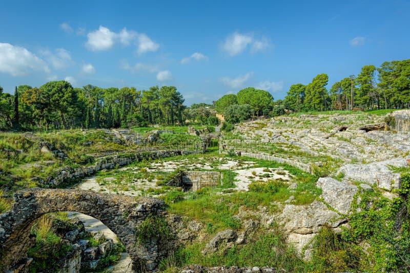 Roman Amphitheater i Syracuse, Sicilien, Italien under blåa himlar arkivbilder