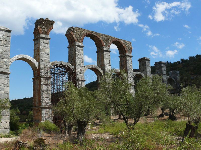 Roman aquaduct tussen olijfbomen stock afbeelding