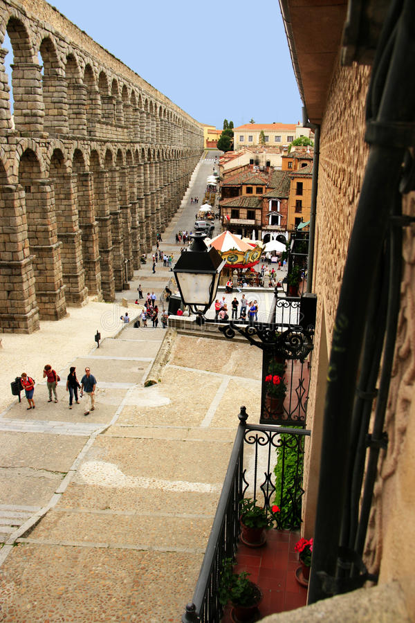 Roman aqueduct Segovia, Spain. The impressive structure of the roman built aqueduct now halving the town center of Segovia rises above medieval houses royalty free stock photography