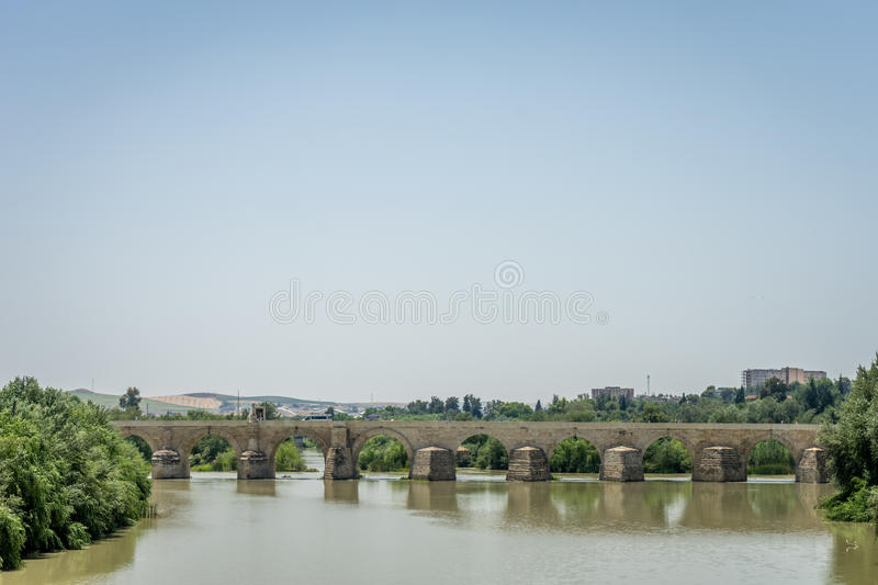 The Roman bridge of Cordoba on the Guadalquivir river. Profile side view of the Roman bridge of Cordoba on the Guadalquivir river on a bright sunny day with blue royalty free stock photo