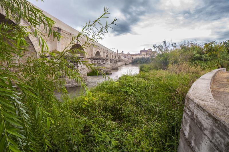 Roman bridge from the left bank reedbeds of Guadalquivir River, Cordoba, Spain royalty free stock photography