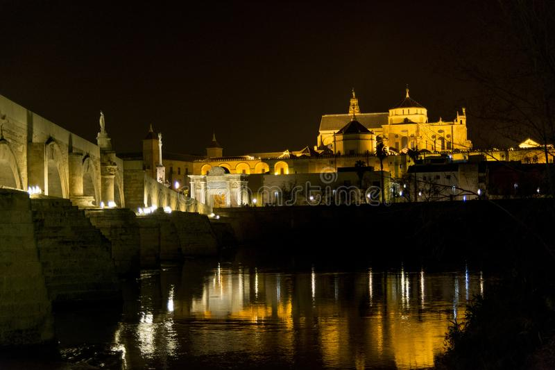 Great Mosque of Cordoba with the Guadalquivir River in the foreground at night royalty free stock images