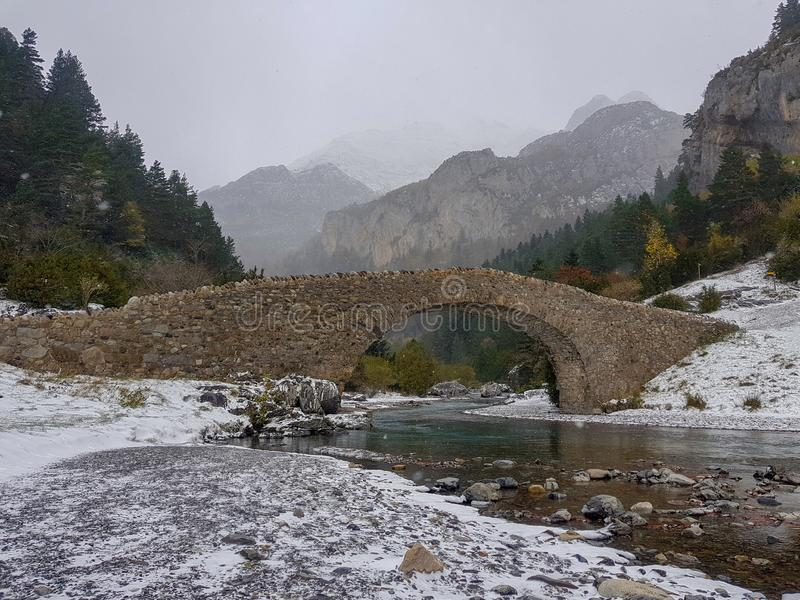 Roman bridge over the Bujaruelo River in the Ordesa National Park in Huesca, Spain. Image of cloudy day with the first snowfalls stock photo