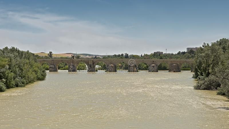 Roman bridge over Guadalquivir river in Cordoba. Roman bridge over Guadalquivir river with green borders with trees and mountains in the background in Cordoba royalty free stock photo