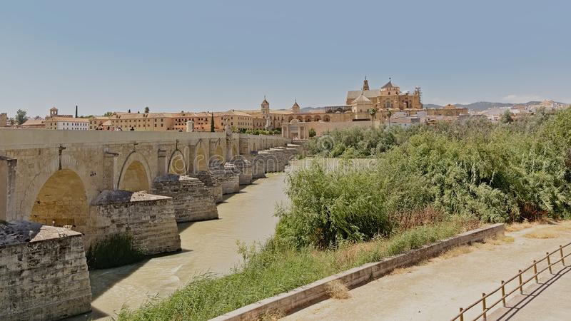 Roman bridge over Guadalquivir river and Mosque cathedral of n Cordoba. Andalusia, spain, view from the green embankment on the other side of the water stock photo