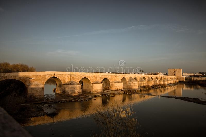 Roman bridge at sunset in Cordoba. With the Guadalquivir river stock image