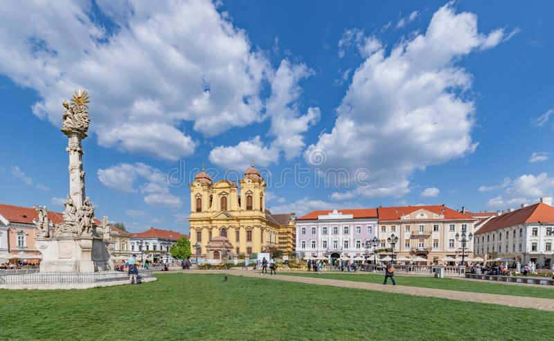 Statue of Holy Trinity and St. George's Roman Catholic Cathedral in Union Square in Timisoara. Romania. The Roman Catholic Cathedral represents the stock photos