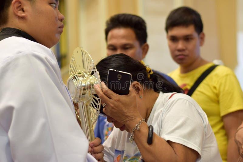 Roman Catholic Women wordt gegeven zeldzame kans om Heilige Monstrans tijdens een stadsfestiviteit te kussen stock afbeelding