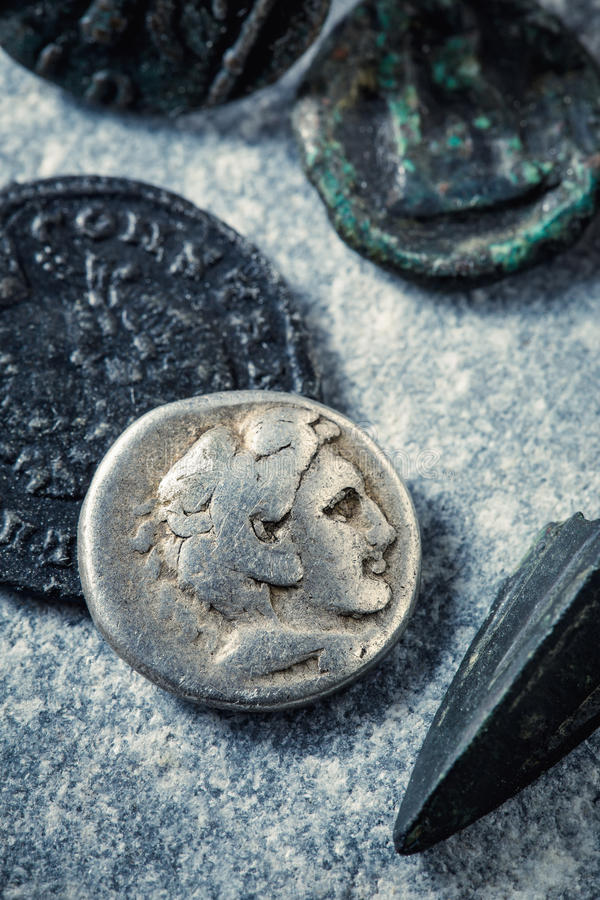 Roman coins and arrowhead. On stone surface royalty free stock images