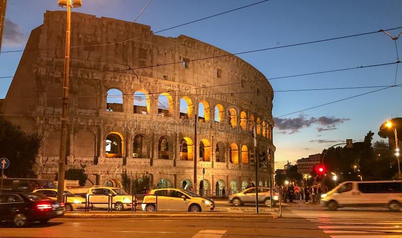 Roman Colosseum iluminou-se acima na noite, com tráfego no primeiro plano fotos de stock royalty free