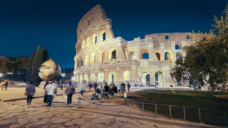 Roman Colosseum and Tourists at Night in Rome, Italy, people blurred royalty free stock images