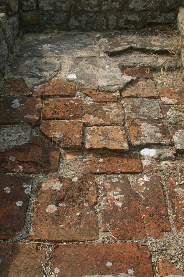 Roman villa floor tiles. Clay tiles on the floor of an excavated roman villa in the UK. The base of the walls are visible. Lichens on the tiles royalty free stock photo