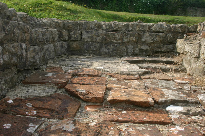 Roman villa floor tiles. Clay tiles on the floor of an excavated roman villa in the UK. The base of the walls are visible. Lichens on the tiles royalty free stock photography