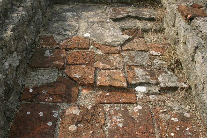 Roman villa floor tiles. Clay tiles on the floor of an excavated roman villa in the UK. The base of the walls are visible. Lichens on the tiles royalty free stock images