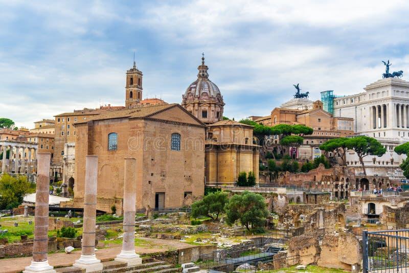 roman fora fördärvar Curia Julia, romerska kolonner och kyrka av Santi Luca e Martina rome italy royaltyfria bilder