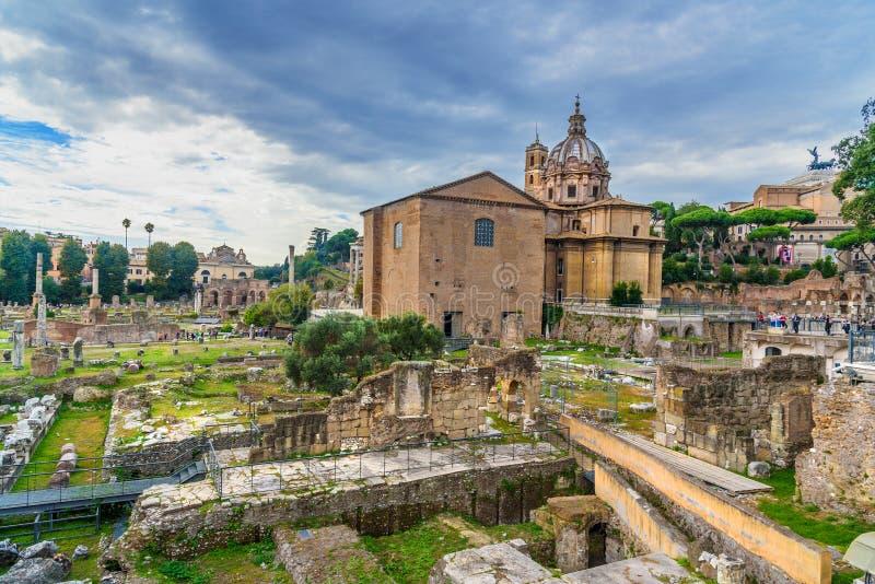 roman fora fördärvar Curia Julia, romerska kolonner och kyrka av Santi Luca e Martina rome italy royaltyfri bild