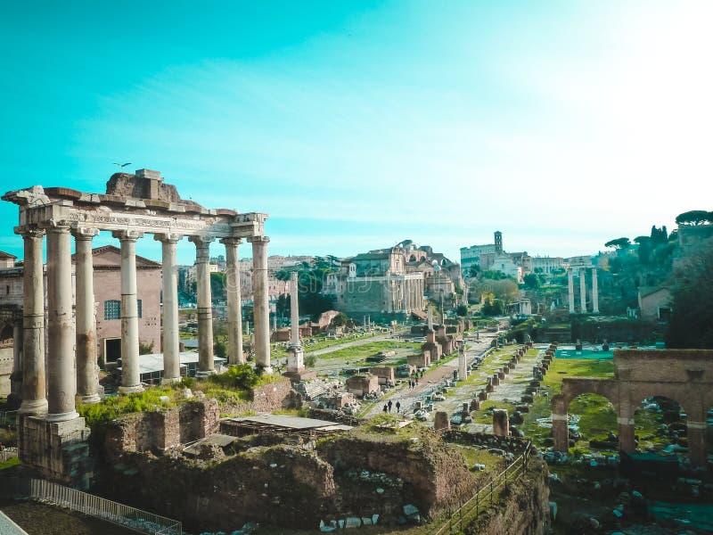 Roman Forum i mitten - kolonner av templet Saturn royaltyfria bilder