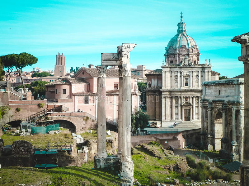 Roman Forum i mitten - kolonner av templet Saturn, Santi Luca e Martino royaltyfria bilder