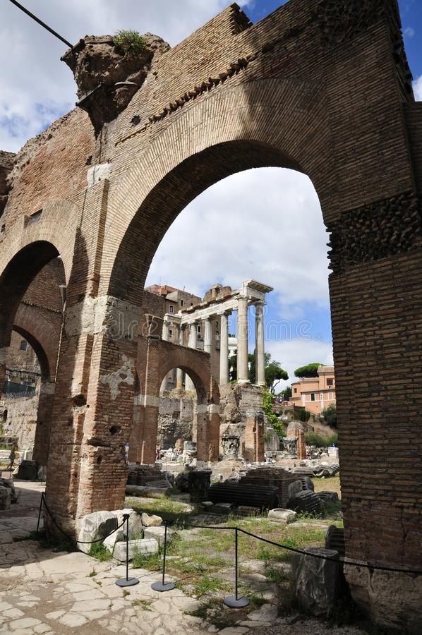 Roman Forum North. Ancient architectural fragments: Arches and view of the Temple of Saturn portrait mode stock photos