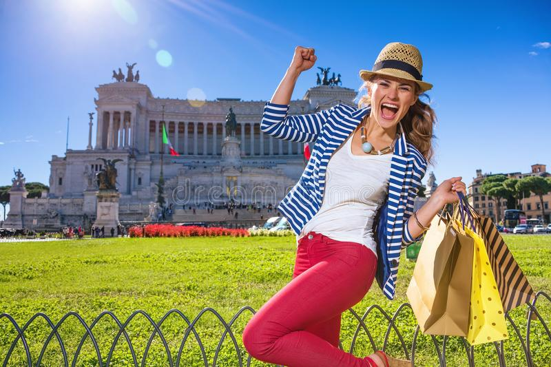 Cheerful woman in Rome, Italy with shopping bags rejoicing royalty free stock image