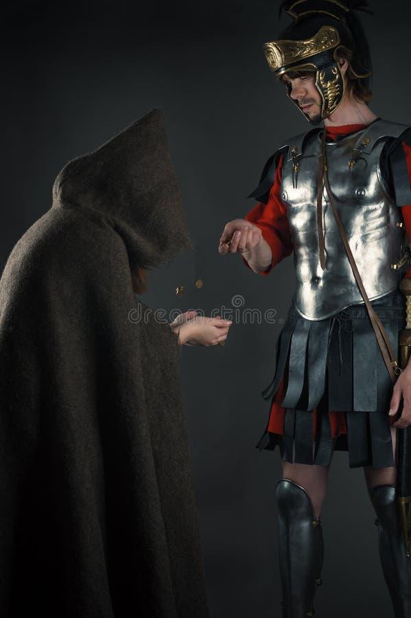 Roman legionary gives a beggar a coin stock photography