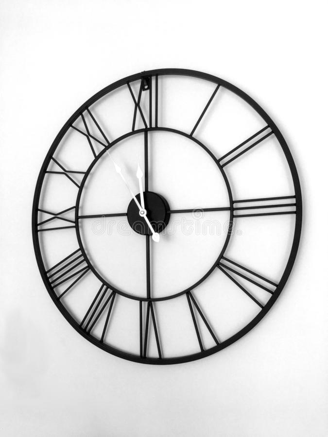 A Roman numeral clock hanging on the wall black and white stock photography
