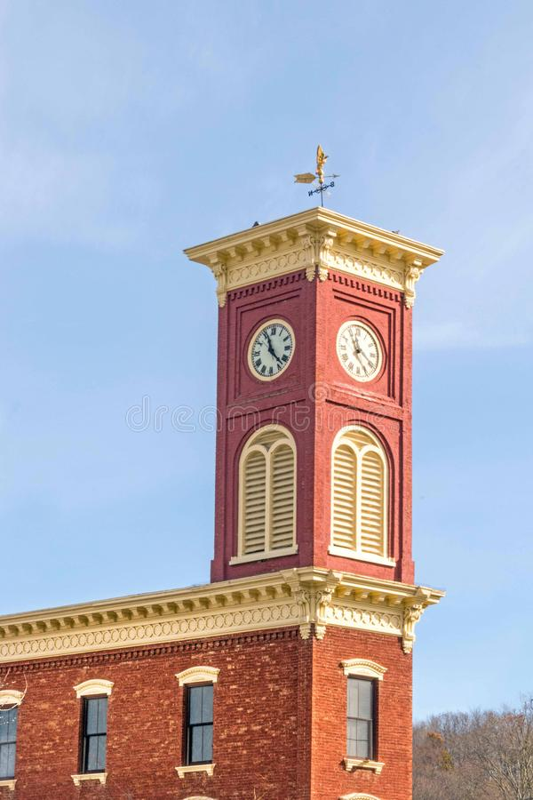 Roman numeral clock tower building. Landmark pendulum clock only one of its kind still in  original condition, brick building former fire company, blue sky royalty free stock images