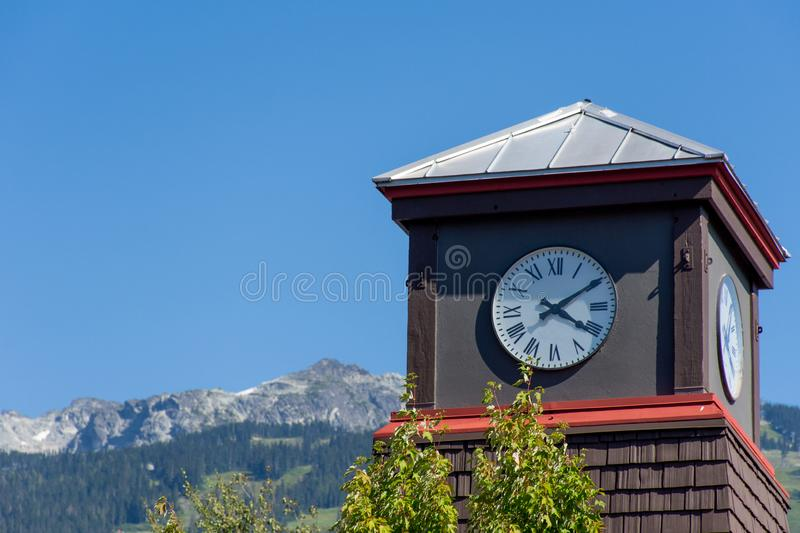 Roman Numeral Clock Tower with rocky mountains and blue sky in the background.  stock image