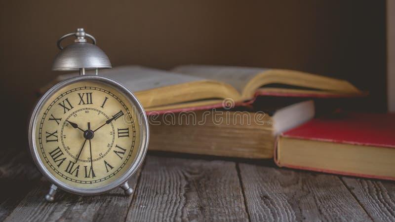 Roman Numeral en despertador del vintage y los wi abiertos del fondo del libro fotografía de archivo