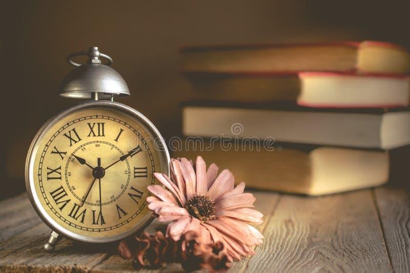 Roman Numeral no despertador do vintage e na pilha de fundo do livro imagem de stock