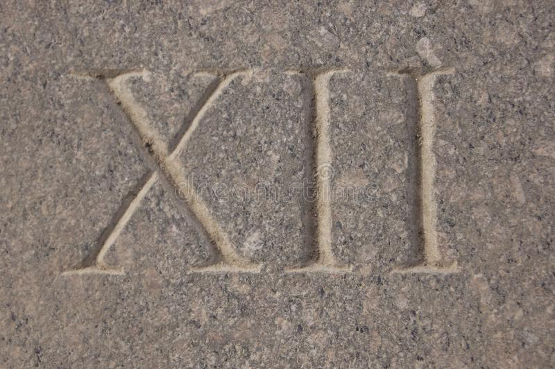 Roman numeral - twelve carved in stone. The Roman numerals are the numbers used by the ancient Romans in their non-positional number system royalty free stock photo