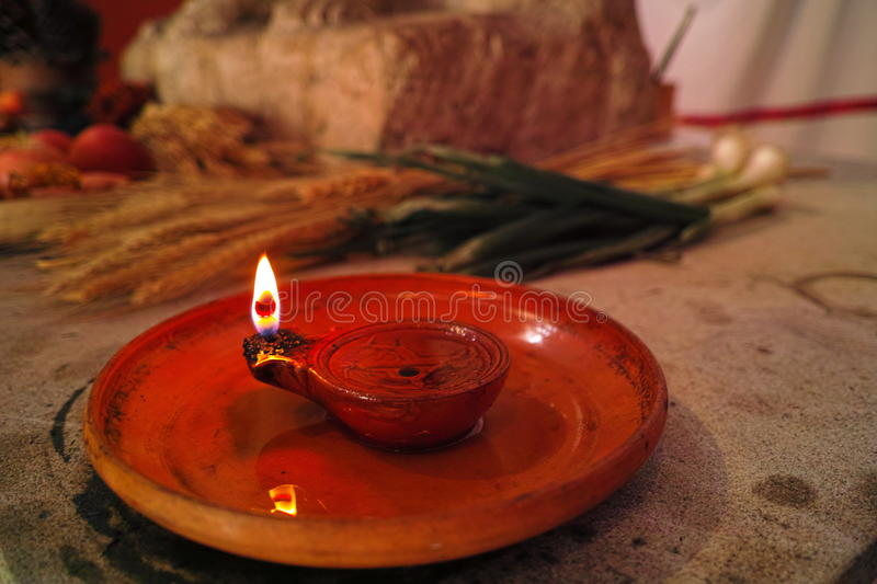Roman oil lamp on thanksgiving table. A decorative Roman oil lamp kindled on a table at thanksgiving. A replicated scene how Romans lived royalty free stock photo