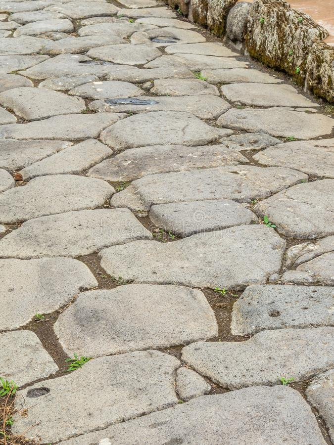 Streets and villas of Pompeii, Italy. World Heritage List. Roman road in the ancient Roman city of Pompeii, near modern Naples in Italy. Rutted, diamond royalty free stock photography