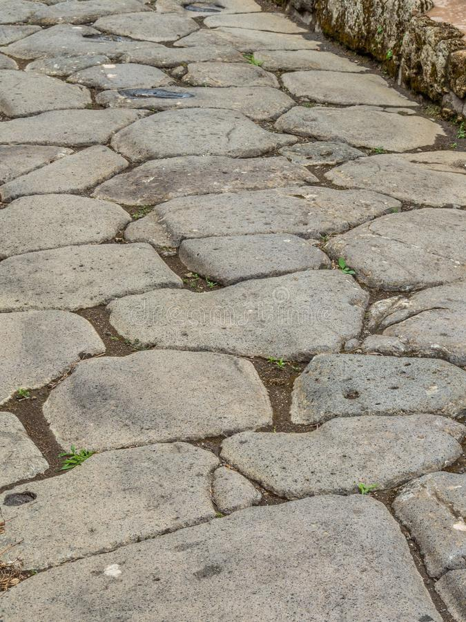 Streets and villas of Pompeii, Italy. World Heritage List. Roman road in the ancient Roman city of Pompeii, near modern Naples in Italy. Rutted, diamond royalty free stock image